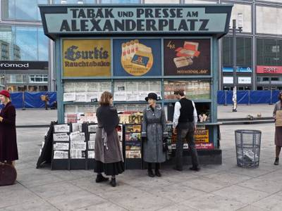Szenenfoto aus Babylon Berlin. – Personen stehen vor einem Zeitungskiosk.