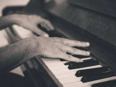 – Hände die Piano spielen in schwarz-weiß, passend zur Veranstaltung der Stiftung Planetarium Berlin.