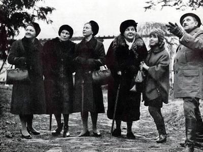 – Schwarz-weißes Szenenfoto: Fünf Frauen und ein Mann betrachten außerhalb des Bildes.