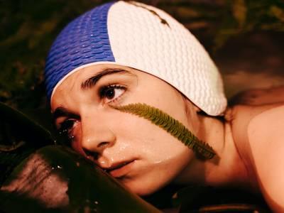 – Das Bild zeigt den Kopf einer Person mit blau-weißer Badehaube. Ihr Kinn befindet sich im Wasser, sie lehnt gegen einen glatten Gegenstand. Auf ihrer Wange liegt ein Farnblatt.