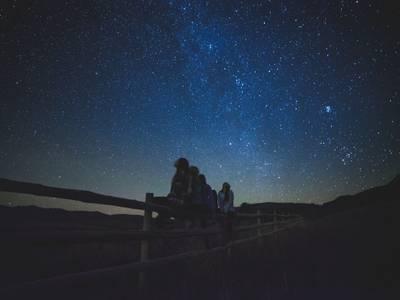 – Zu sehen ist ein dunkler Nachthimmel mit leuchtenden Sternen und Kindern, die in den Himmel schauen, passend zur Veranstaltung der Stiftung Planetarium Berlin.