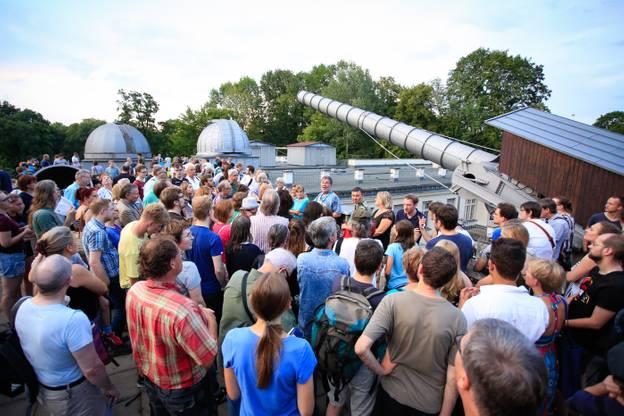 Zu sehen ist das Treptower Riesenfernrohr mit Besucher*innen auf dem Dach der Archenhold-Sternwarte der Stiftung Planetarium Berlin.