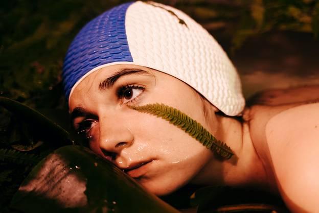 Das Bild zeigt den Kopf einer Person mit blau-weißer Badehaube. Ihr Kinn befindet sich im Wasser, sie lehnt gegen einen glatten Gegenstand. Auf ihrer Wange liegt ein Farnblatt.