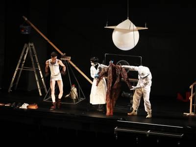 Der Dominoeffekt – Ansicht der Bühne, die aussieht wie eine Art Labor mit einer Wippe, einem Ball in der Luft und Holzbarrikaden