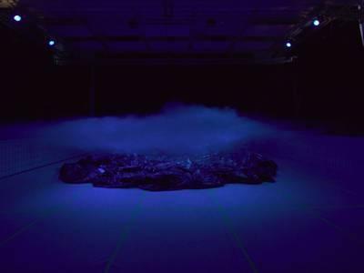 Strange Garden – Nebel breitet sich auf einer blau beleuchteten Bühne aus, auf dem Boden liegt eine Plane.