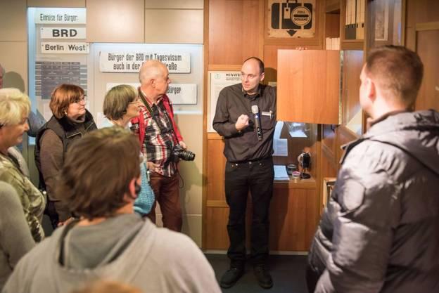 Ein Gruppenbegleiter spricht zu Besuchern und Besucherinnen im Tränenpalast – Ein Gruppenbegleiter spricht zu Besuchern und Besucherinnen im Tränenpalast